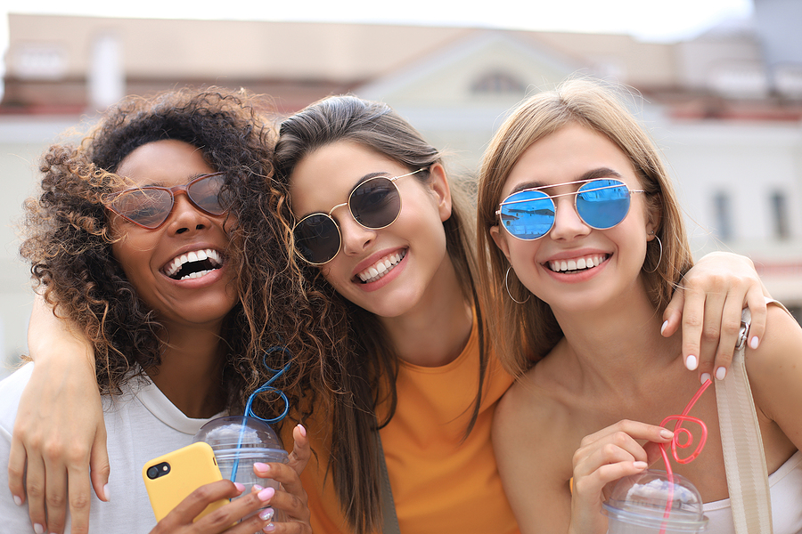 Three trendy cool hipster girls, friends drink cocktail in urban city background.